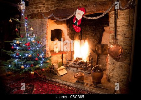 Inglenook fireplace in old house with high blazing log fire and decorated Christmas tree, stocking and copper kettle. - Stock Photo