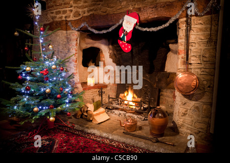 Inglenook fireplace in old house with low burning log fire and decorated Christmas tree, stocking and copper kettle. - Stock Photo