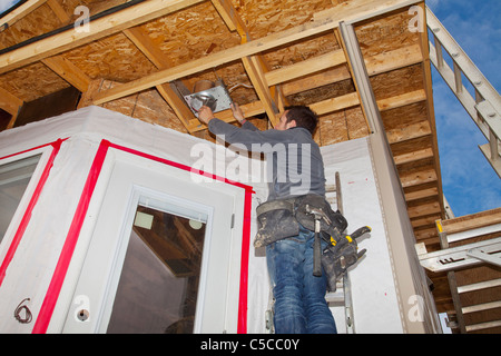Electrician Installing Light Fixtures; Edmonton, Alberta, Canada - Stock Photo