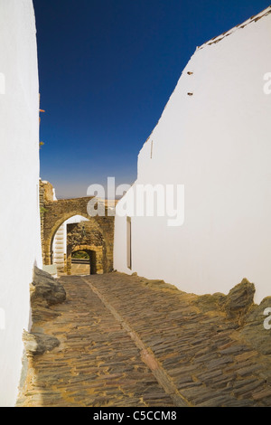 Whitewashed Buildings And Alleyway Paved With Cobblestones Inside The Walls Of The Old Castle; Monsaraz, Portugal - Stock Photo
