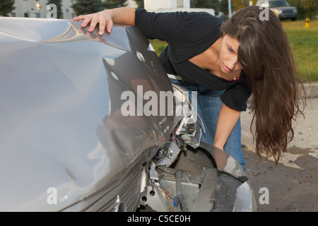 Young Woman With Vehicle That Has Been In A Collision; Edmonton, Alberta, Canada - Stock Photo