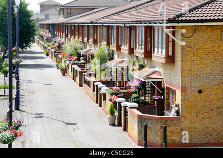 Modern terraced housing in East London with small front garden opening onto wide canal side pedestrian walkway England - Stock Photo