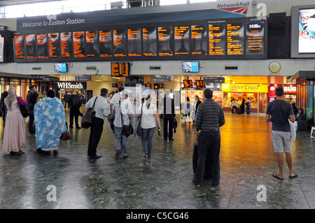 Euston train station concourse travellers viewing train departure board London England UK - Stock Photo