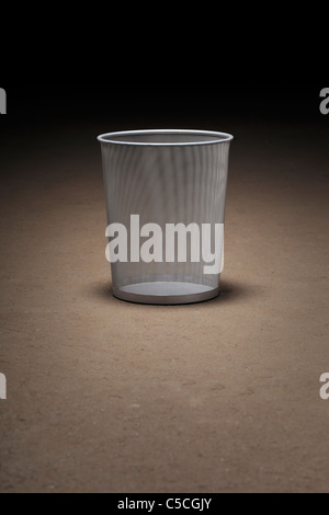 Empty wastepaper basket on dirty concrete floor - Stock Photo
