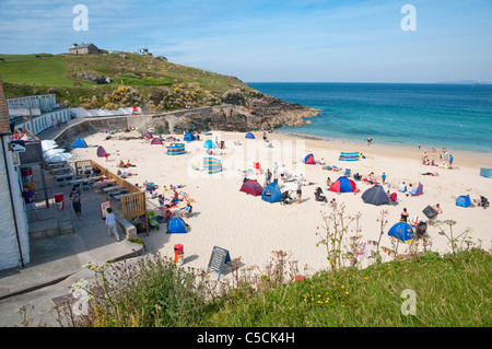 Porthgwidden - popular family beach and cafe ( left ) in St Ives - with a backdrop of The Island / St Ives Head, - Stock Photo