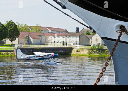 A Loch Lomond Seaplane is moving down river on the Clyde in Glasgow passing Govan & the Riverside Museum with tall - Stock Photo
