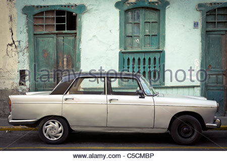 Old Mercedes car parked in front of a run-down abandoned building, Trujillo, La Libertad, Peru - Stock Photo