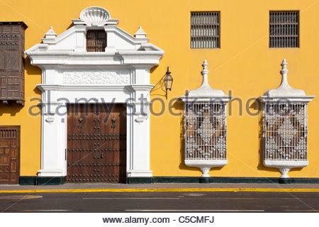 Facade of a brightly colored colonial mansion on the Plaza de Armas, Trujillo, La Libertad, Peru - Stock Photo