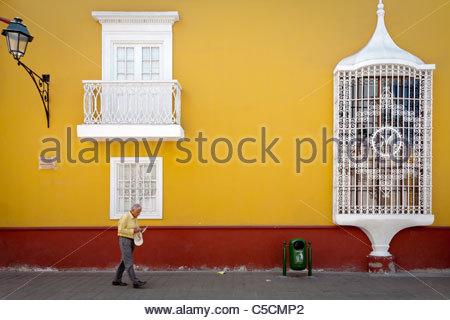 Old man walking in front of Casa de la Emancipacion, Trujillo, La Libertad, Peru - Stock Photo