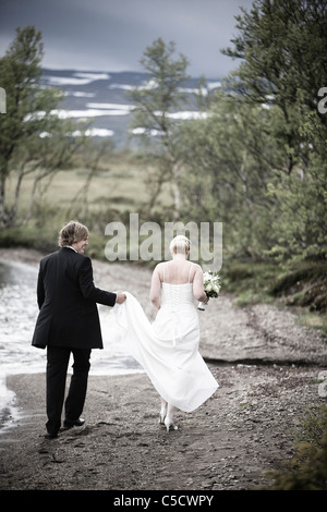 Rear view of a bride holding groom's grown while walking on beach with trees in background - Stock Photo