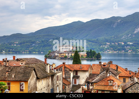 View of the island of San Giulio in Lake Orta on the roofs of Orta - Stock Photo