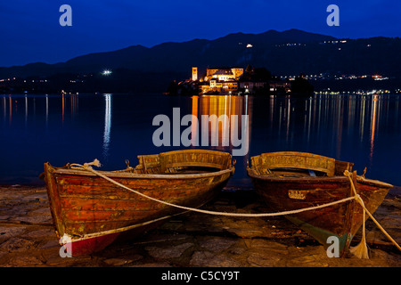 Island of San Giulio on Lake Orta in the night with two rowing boats in the foreground - Stock Photo