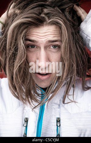 Close-up portrait of a long-haired guy scratching his hair - Stock Photo