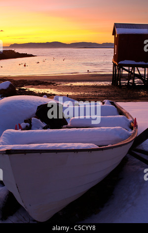 Abandoned snow covered boat with lake in the background at dusk - Stock Photo