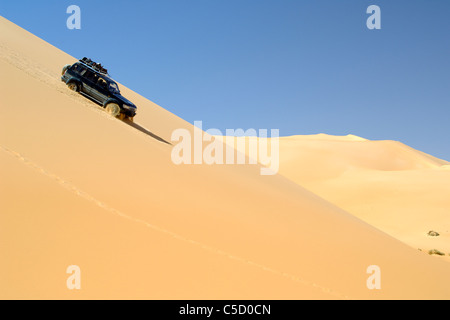Side view of an off road vehicle on the sand dune slope against clear blue sky at Libya - Stock Photo