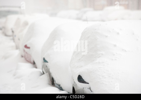 Snow covered cars parked in a row - Stock Photo
