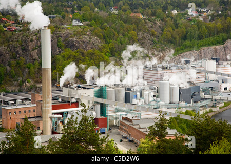 Overview of industrial area with chimneys emitting smoke against trees at Halden, Norway - Stock Photo