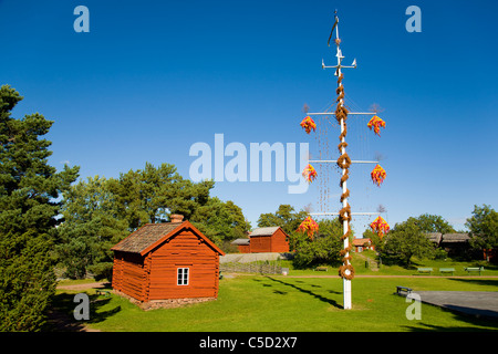 Maypole by homesteads and trees against clear blue sky at Aland island - Stock Photo