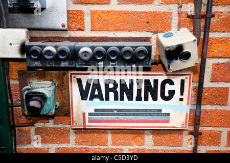 Close-up of an old warning sign and actuator on brick wall - Stock Photo