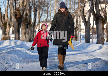 Woman and a little girl in winter wear holding hands and walking along the trees - Stock Photo