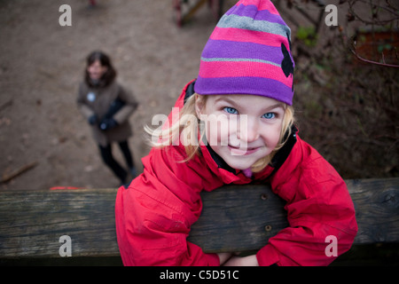 Portrait of a little girl in winter wear hanging on to a log with blurred woman in the background - Stock Photo