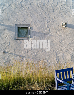 Small window on stucco with cropped empty bench and grass in foreground - Stock Photo