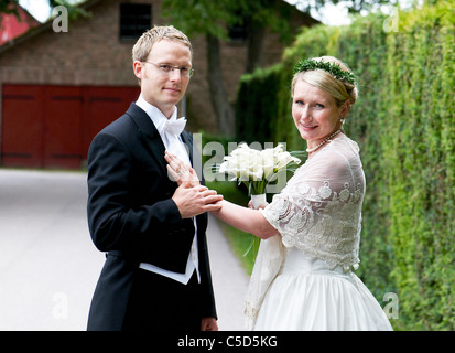 Side view portrait of a bride and groom on the path along creepers - Stock Photo
