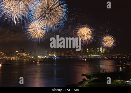 The Macy's 4th of July fireworks show lights the sky over Hudson River in New York City. - Stock Photo