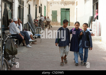 Travel Tunisia.Schoolchildren on the way home from school  in the desert town of Tozeur - Stock Photo