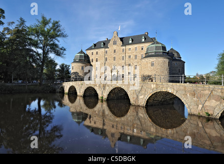 Reflection of the castle with blue sky and arched bridge in the peaceful river in Orebro, Sweden - Stock Photo