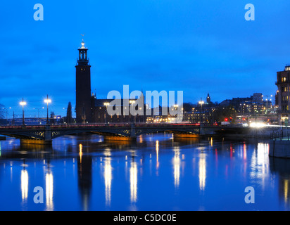City hall and buildings against blue sky reflected in peaceful lake at Stockholm, Sweden - Stock Photo
