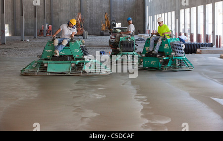 Cement Polishers Riding Power Trowels over freshly poured concrete can smooth the surface to a glass-like finish! - Stock Photo