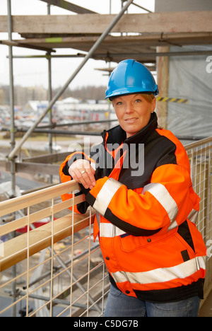 Portrait of a confident female construction engineer in blue hardhat - Stock Photo