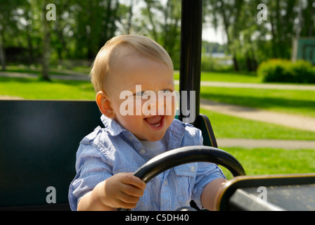 Happy little boy driving cropped toy car in the playground - Stock Photo