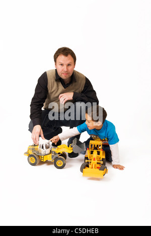 Portrait of a man by son playing with toy vehicles against white background - Stock Photo
