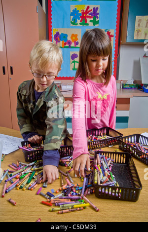 Kindergarten children in San Clemente, CA, collect and organize a table of classroom objects including crayons and - Stock Photo