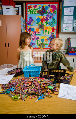 Kindergarten children in San Clemente, CA, contemplate a table full of classroom objects including crayons and worksheets. - Stock Photo