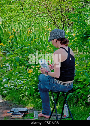 A young woman artist works on a sketch while sitting in a grove of iris at the Brooklyn Botanic Garden in New York - Stock Photo