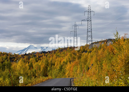 Power lines against the clouds with autumn trees and country road in foreground - Stock Photo