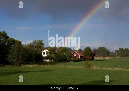 Rainbow behind country houses and trees with fields in foreground - Stock Photo