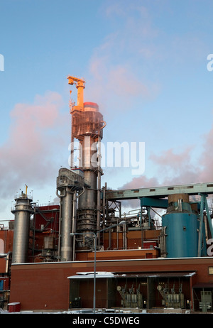 Low angle view of factory chimney emitting smoke against clear sky - Stock Photo