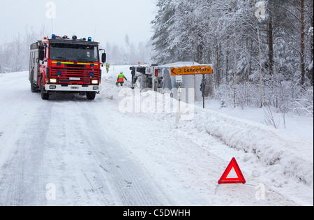 Fire brigade by a vehicle in ditch on winter road with warning sign in foreground - Stock Photo