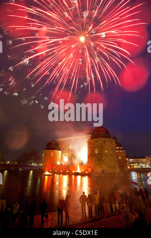 View of people watching fireworks over Orebro castle at night in Sweden - Stock Photo