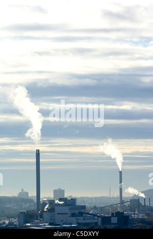 Chimneys emitting smoke at the industrial area against the sky - Stock Photo