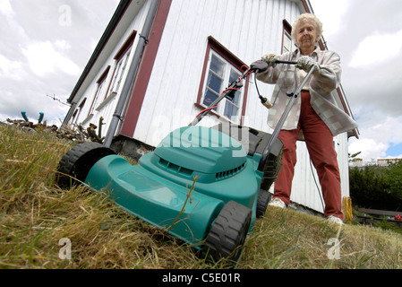 Low angle view of a senior woman mowing the yard against house and clouds - Stock Photo