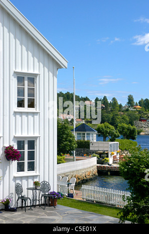 Houses by the cropped lake with trees against blue sky - Stock Photo