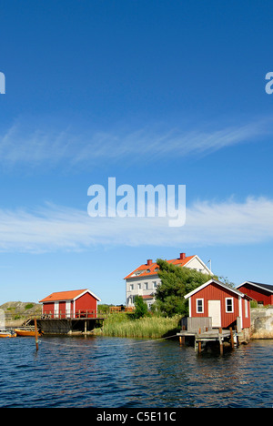 Peaceful lake with houses against blue sky and clouds in the background - Stock Photo