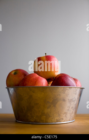 Close-up of a bowl of apples on table against gray background - Stock Photo