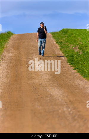 Man in casuals walking on the dirt country road along landscape - Stock Photo