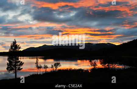 Scenic and peaceful view of silhouette mountains and lake against dramatic sky at dusk - Stock Photo